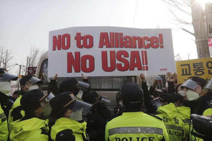 Protesters hold up a banner during a rally against a visit of U.S. Defense Secretary Lloyd Austin and Secretary of State Antony Blinken as police stand guard outside Foreign Ministry in Seoul, South Korea, Thursday, March 18, 2021. North Korea said Thursday it will ignore a U.S. offer for talks unless it withdraws its hostile policy, days after Washington reached out to Pyongyang in a bid to resume nuclear negotiations. (AP Photo/Ahn Young-joon)