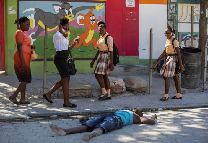 Pedestrians walk past a body of a prison inmate lying on a street near the Croix-des-Bouquets Civil Prison after an attempted breakout, in Port-au-Prince, Haiti, Thursday, Feb. 25, 2021. At least seven people were killed and one injured on Thursday after eyewitnesses told The Associated Press that several inmates tried to escape from a prison in Haiti's capital. (AP Photo/Dieu Nalio Chery).