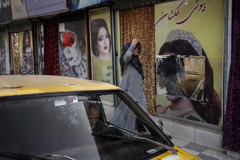 An Afghan woman walks past beauty salons with defaced window decorations, in Kabul, Afghanistan, Sunday, Sept. 12, 2021. Since the Taliban gained control of Kabul, several images depicting women outside beauty salons have been removed or covered up. (AP Photo/Bernat Armangue)