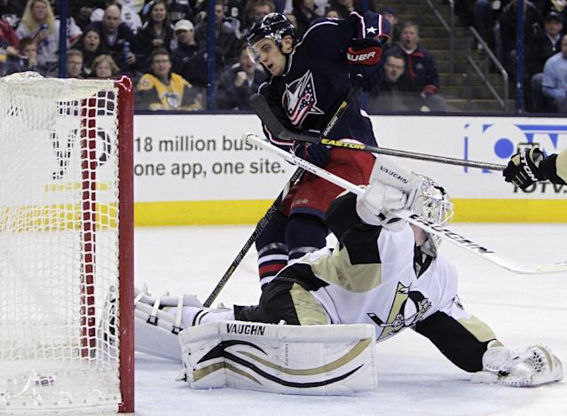 Columbus Blue Jackets' Corey Tropp, top, scores a goal against Pittsburgh Penguins' Jeff Zatkoff during the second period of an NHL hockey game on Sunday, Dec. 29, 2013, in Columbus, Ohio. (AP Photo/Jay LaPrete)