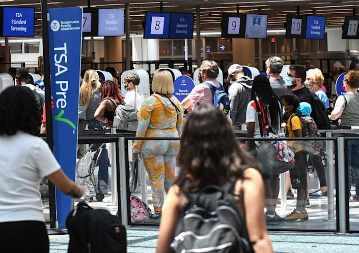 Travelers wait in line at a Transportation Security Administration (TSA) screening checkpoint at Orlando International Airport on the Friday before Memorial Day. (Photo by Paul Hennessy/SOPA Images/LightRocket via Getty Images)