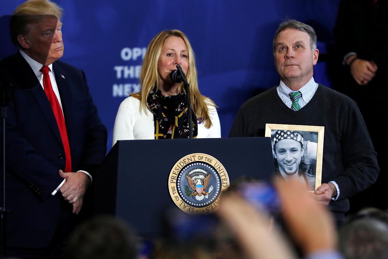 Grieving parents Jim and Jeanne Moser, holding a picture of their son Adam who died from a drug overdose, join U.S. President Donald Trump onstage during his remarks on the U.S. opioid crisis, at Manchester Community College in Manchester, New Hampshire, U.S., March 19, 2018. REUTERS/Jonathan Ernst