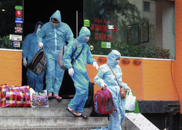 People walk toward an ambulance to be driven to a hospital for quarantine relating to a suspected COVID-19 case in Hanoi, Vietnam, Wednesday, July 29, 2020. Vietnam has locked down Da Nang, its third-largest city, for two weeks after 15 cases of COVID-19 were found in a hospital. (AP Photo/Hau Dinh)