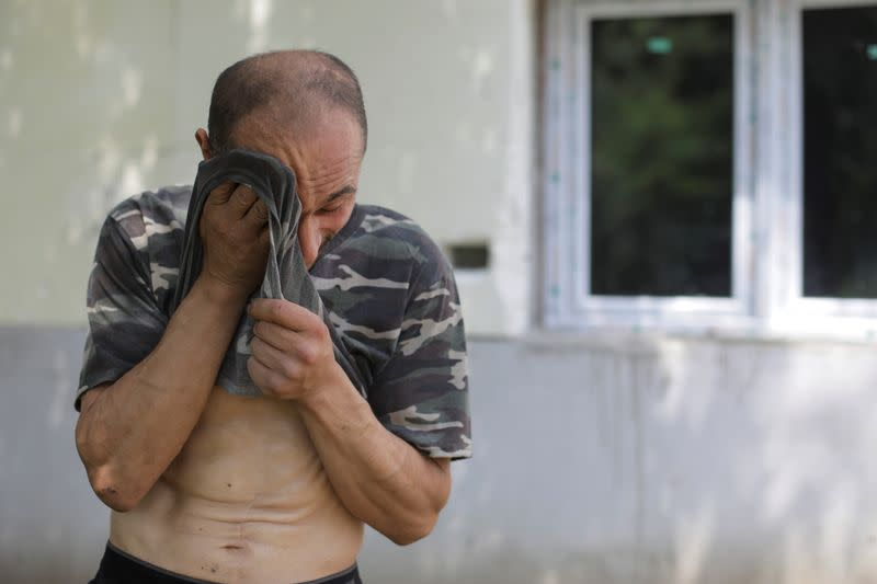 Alberto Gogu wipes sweat off his forehead after clearing debris in his courtyard