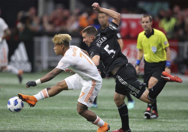 Atlanta United forward Josef Martinez, left, works against Sporting Kansas City defender Matt Besler for the ball during the first half of an MLS soccer match Wednesday, May 9, 2018, in Atlanta. (Curtis Compton/Atlanta Journal-Constitution via AP)