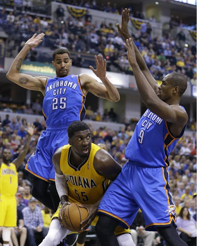 Indiana Pacers center Roy Hibbert, center, is trapped between Oklahoma City Thunder guard Thabo Sefolosha (25) and forward Serge Ibaka in the second half of an NBA basketball game in Indianapolis, Sunday, April 13, 2014. The Pacers defeated the Thunder 102-97. (AP Photo/Michael Conroy)