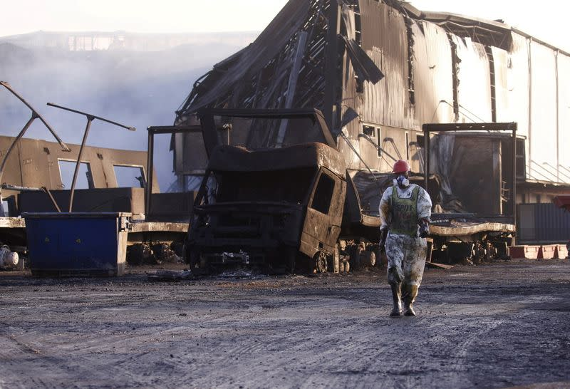 FILE PHOTO: A member of a hazardous waste cleanup crew walks to clean up a burned warehouse, in Durban