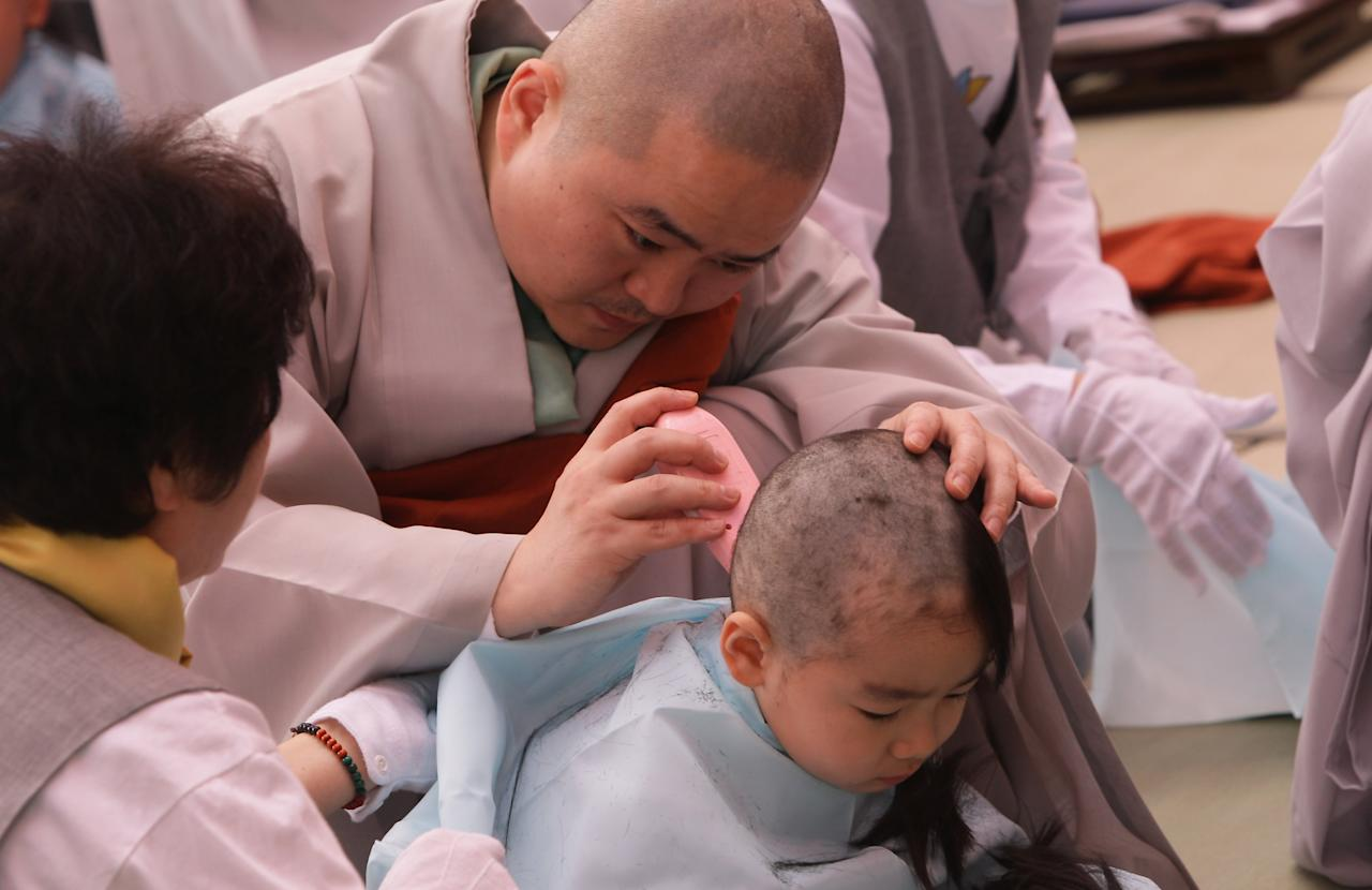 SEOUL, SOUTH KOREA - MAY 03:  A child gets his head shaved by a Buddhist monk during the 'Children Becoming Buddhist Monks' ceremony forthcoming buddha's birthday at a Chogye temple on May 3, 2013 in Seoul, South Korea. The children will stay at the temple to learn about Buddhism for 14 days. Buddha was born approximately 2,557 years ago, and although the exact date is unknown, Buddha's official birthday is celebrated on the full moon in May in South Korea, which is on May 17 this year.  (Photo by Chung Sung-Jun/Getty Images)