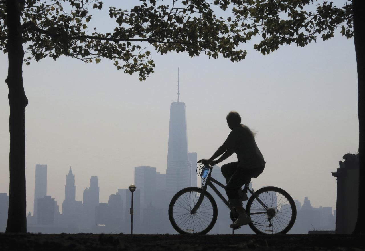REFILE - UPDATING CAPTION  A woman rides her bicycle past the skyline of New York's Lower Manhattan and One World Trade Center in a park along the Hudson River in Hoboken, New Jersey, September 11, 2013. Americans marked the 12th anniversary of the 9/11 attacks with solemn ceremonies and pledges not to forget the nearly 3,000 killed when hijacked jetliners crashed into the World Trade Center, the Pentagon and a Pennsylvania field, in 2001. REUTERS/Gary Hershorn (UNITED STATES - Tags: CITYSCAPE POLITICS ANNIVERSARY DISASTER)