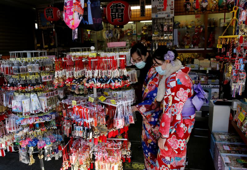Tourists wearing Kimono and surgical masks visit a souvenir shop near Sensoji temple in Tokyo