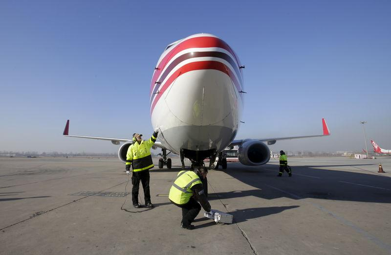 Members of the ground service crew check a China United Airlines aircraft after it landed at the Nanyuan Airport in Beijing