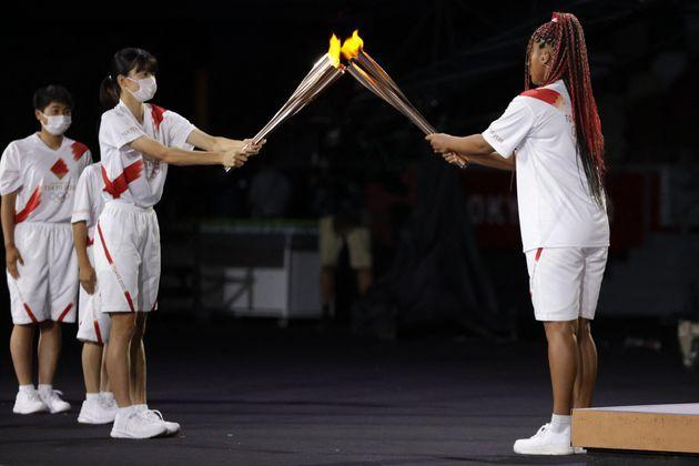 Japan's tennis player Naomi Osaka (R) lights her Olympic Torch before lighting the flame of hope in the Olympic Cauldron during the opening ceremony of the Tokyo 2020 Olympic Games on July 23. (Photo: HANNAH MCKAY via Getty Images)