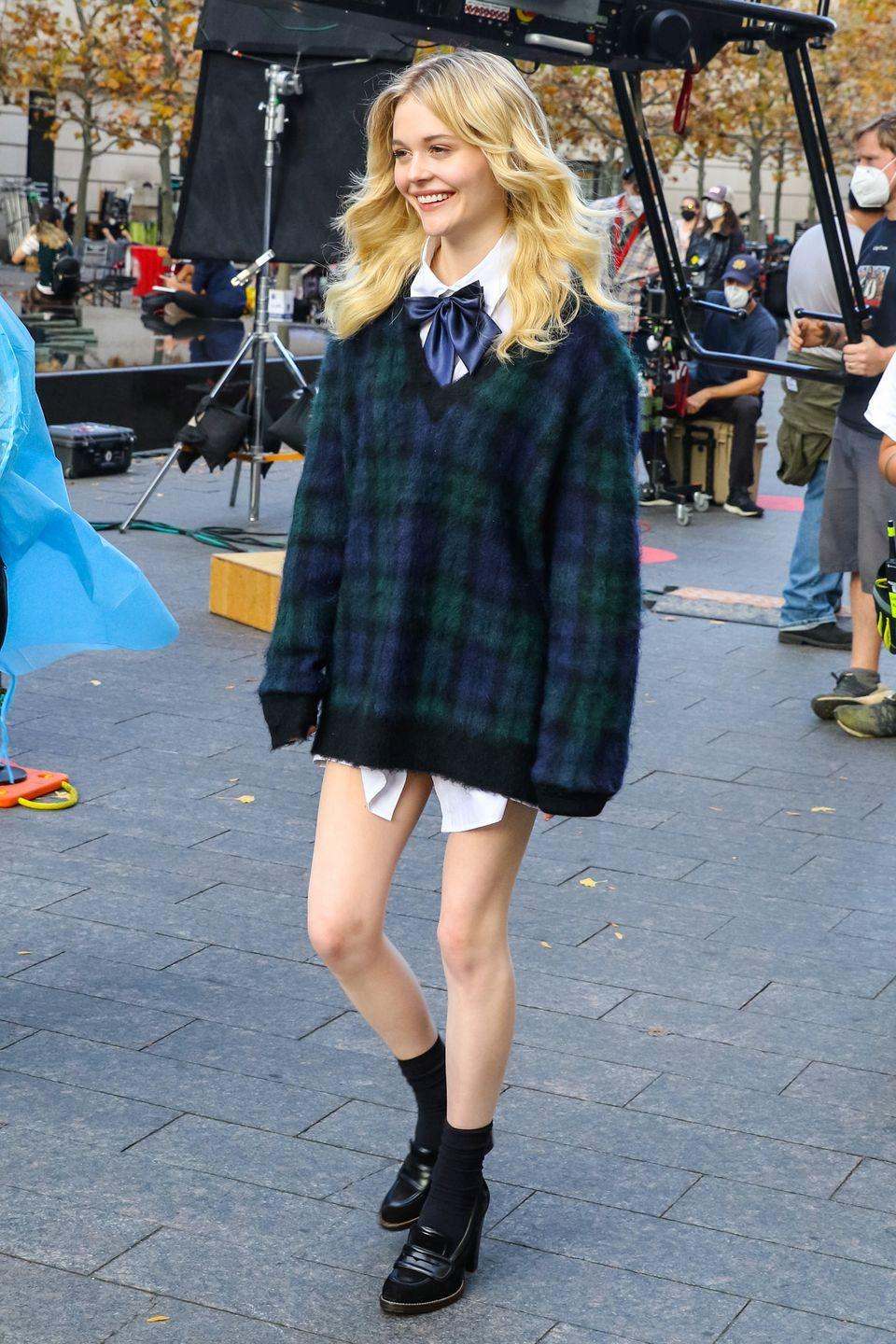<p>Emily Alyn Lind rocks a preppy no-pants look featuring an oversized sweater, pussy bow blouse, black socks, and heeled loafers. </p>