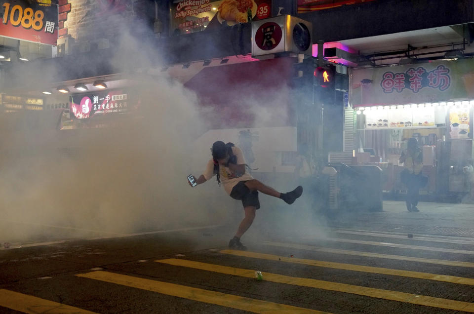 "A protester reacts to tear gas during a confrontation with police in Hong Kong on Sunday, Oct. 27, 2019. Hong Kong police fired tear gas Sunday to disperse a rally called over concerns about police conduct in monthslong pro-democracy demonstrations, with protesters cursing the officers and calling them ""gangster cops."" (AP Photo/Vincent Yu)"