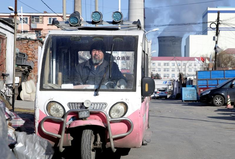 A man is seen in a motor tricycle near a coal-fired power plant in Harbin