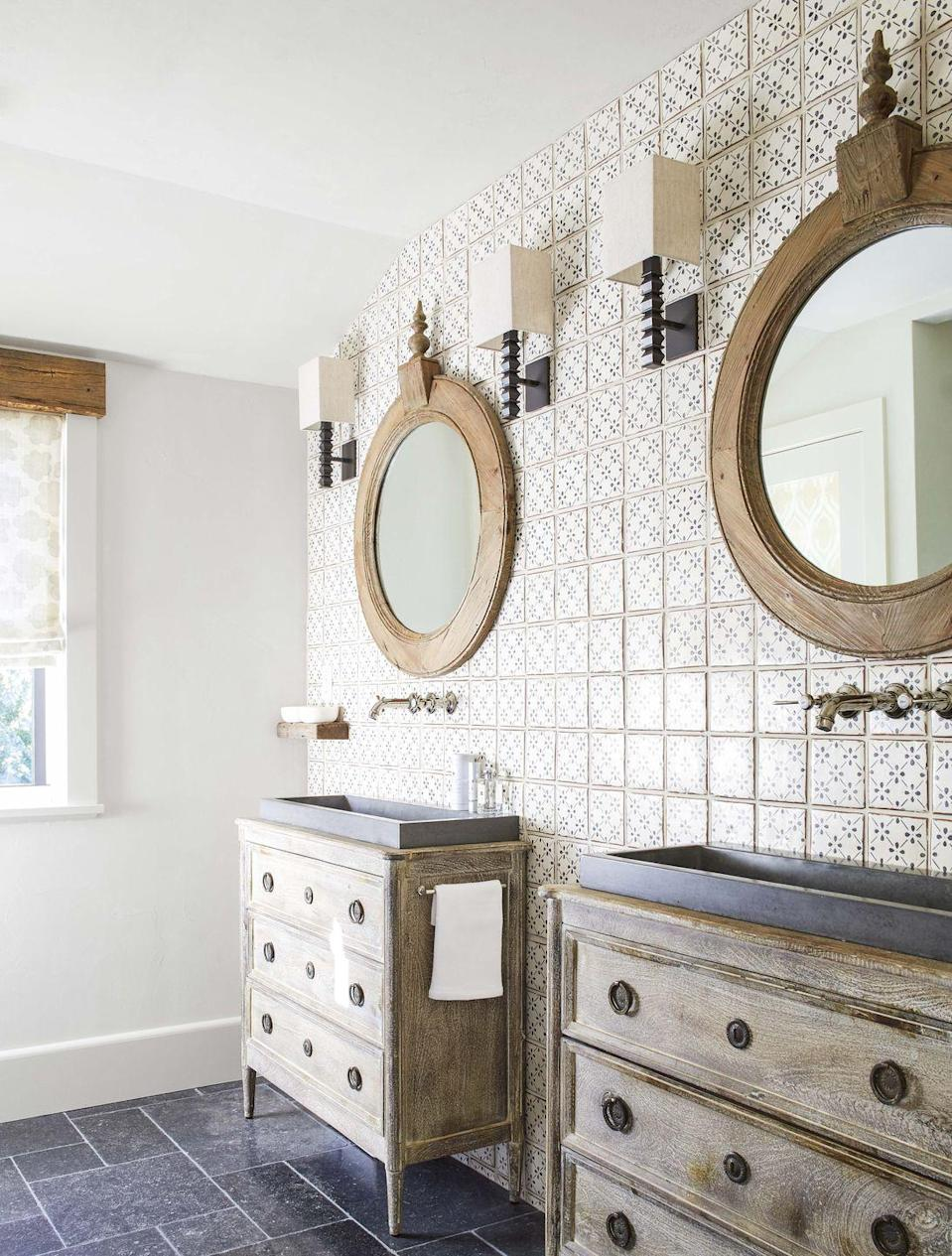 """<p>In this <a href=""""https://www.housebeautiful.com/design-inspiration/house-tours/a30696947/lisa-tharp-new-england-home/"""" rel=""""nofollow noopener"""" target=""""_blank"""" data-ylk=""""slk:castle-inspired home by Lisa Tharp,"""" class=""""link rapid-noclick-resp"""">castle-inspired home by Lisa Tharp,</a> the designer continued the rustic French country theme into the bathroom with two wooden chests in lieu of traditional sink vanities and a painted tile wall for added texture. </p>"""