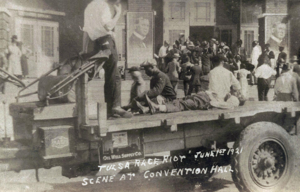 FILE - This photo provided by the Department of Special Collections, McFarlin Library, The University of Tulsa shows a truck parked in front of the Convention Hall with a Black man whose condition is unknown lying on the bed of a truck during the Tulsa Race Massacre in Tulsa, Okla., on June 1, 1921. A man in civilian clothing, left, stands guard. (Department of Special Collections, McFarlin Library, The University of Tulsa via AP, File)