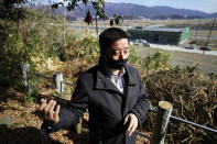 Michihiro Kono, president of Yagisawa Shoten Co., stands at a hill overlooking a newly built factory where his company's headquarters was located before the 2011 tsunami, Friday, March 5, 2021, in Rikuzentakata, Iwate Prefecture, northern Japan. Just a month after the tsunami as high as 17 meters (55 feet) smashed into the city of Rikuzentakata, soy sauce maker Kono inherited his family's two-century-old business from his father. Later this year the ninth generation owner of Yagisawa Shoten Co. will open a new factory on the same ground where his family started making soy sauce in 1807. (AP Photo/Eugene Hoshiko)