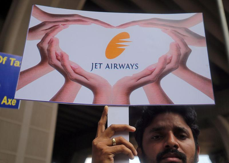 """A Jet Airways employee holds up a placard during a protest demanding to """"save Jet Airways"""" at the Chhatrapati Shivaji Maharaj International Airport in Mumbai"""