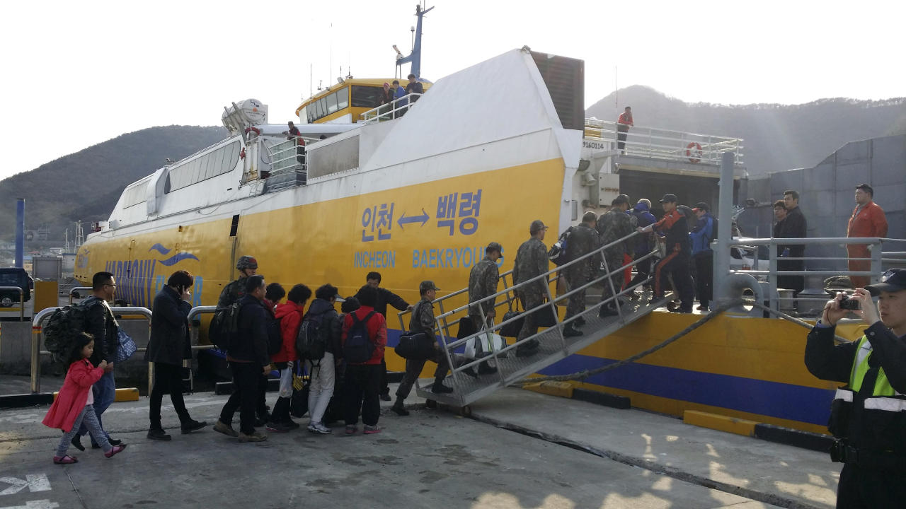 In this photo provided by the Ongjin County, South Korean soldiers and islands' residents reembark a vessel bound for Baengnyeong island, as they evacuate from Daecheong island near the West Sea border with North Korea, Monday, March 31, 2014. North and South Korea fired artillery shells into each other's waters Monday, a flare-up of animosity between the rivals that forced residents of five front-line South Korean islands to evacuate to shelters, South Korean officials said. (AP Photo)
