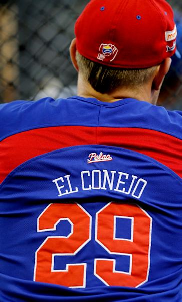 """In this Nov. 27, 2013 photo, C.J. Retherford, a 28-year-old Arizona native, wears a jersey with his nickname """"El Conejo,"""" or """"the Rabbit"""" during a warm-up before a the start of a baseball game at Estadio Universitario in Caracas, Venezuela. Last season Retherford played for the RedHawks of the sister cities of Fargo, North Dakota, and Moorhead, Minnesota. He now plays third base for the Tiburones, or Sharks, in the city of La Guaira outside Caracas, one of the nine """"imports"""" the league allows each team to hire. (AP Photo/Fernando Llano)"""