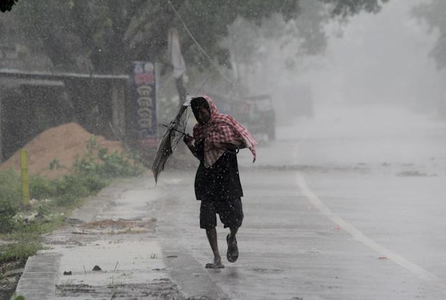 A man boy runs along an embankment ahead of the expected landfall of cyclone Amphan, in Dhamra area of Bhadrak district, 160 km away from the eastern Indian state Odisha's capital city as the Cyclone 'Amphan' cross the Bay of Bengal Sea's eastern coast making devastation on the cyclonic weather wind and rain and make landfall on the boarder of West Bengal and Bangladesh on May 20, 2020. (Photo by STR/NurPhoto via Getty Images)