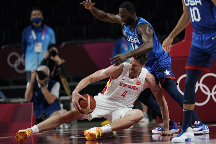 Spain's Pau Gasol (4), on court, and United States' Draymond Green (14) scramble for a ball during men's basketball quarterfinal game at the 2020 Summer Olympics, Tuesday, Aug. 3, 2021, in Saitama, Japan. (AP Photo/Eric Gay)