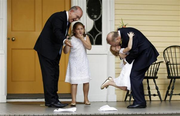 Jonathan Mintz (L), New York City's consumer affairs commissioner, and John Feinblatt (R), a chief adviser to the mayor, embrace their daughters Maeve (2nd L) and Georgia after being married by New York City Mayor Michael Bloomberg at Gracie Mansion in New York July 24, 2011.