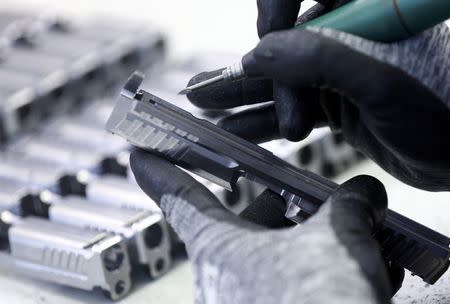 An employee works on a part of a Heckler & Koch P 8 handgun during a guided media tour at their headquarters in Oberndorf, 80 kilometers southwest of Stuttgart, Germany, May 8, 2015. REUTERS/Ralph Orlowski