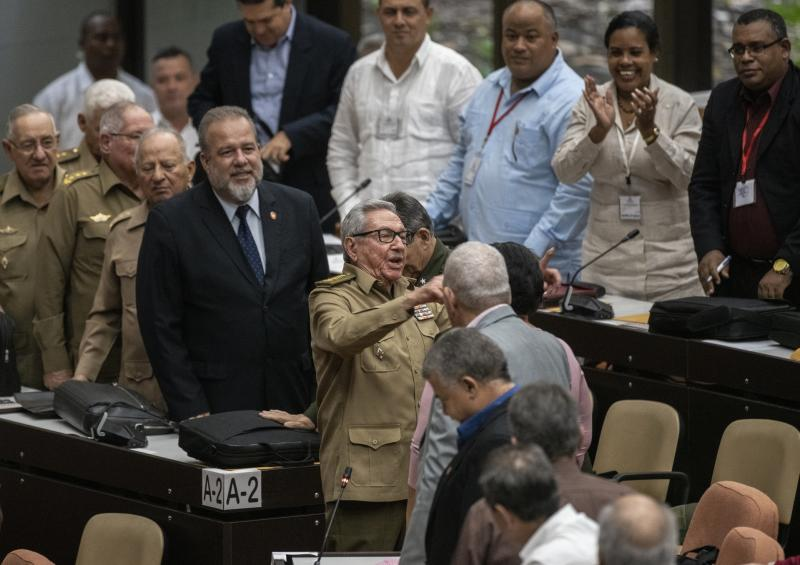 Raul Castro, center, First Secretary of the Communist Party and former president talks with the member of the assembly while Cuban Prime Minister Manuel Marrero Cruz, center left, looks on during the closing session at the National Assembly of Popular Power in Havana, Cuba, Saturday, Dec. 21, 2019. (AP Photo/Ramon Espinosa)