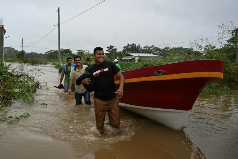 Residents of the town of Morales, Guatemala wade through flood water to safety, as storm Eta pounds the region