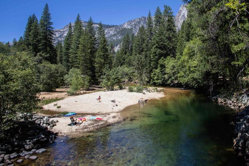 Visitors sunbathe at Merced River in Yosemite.