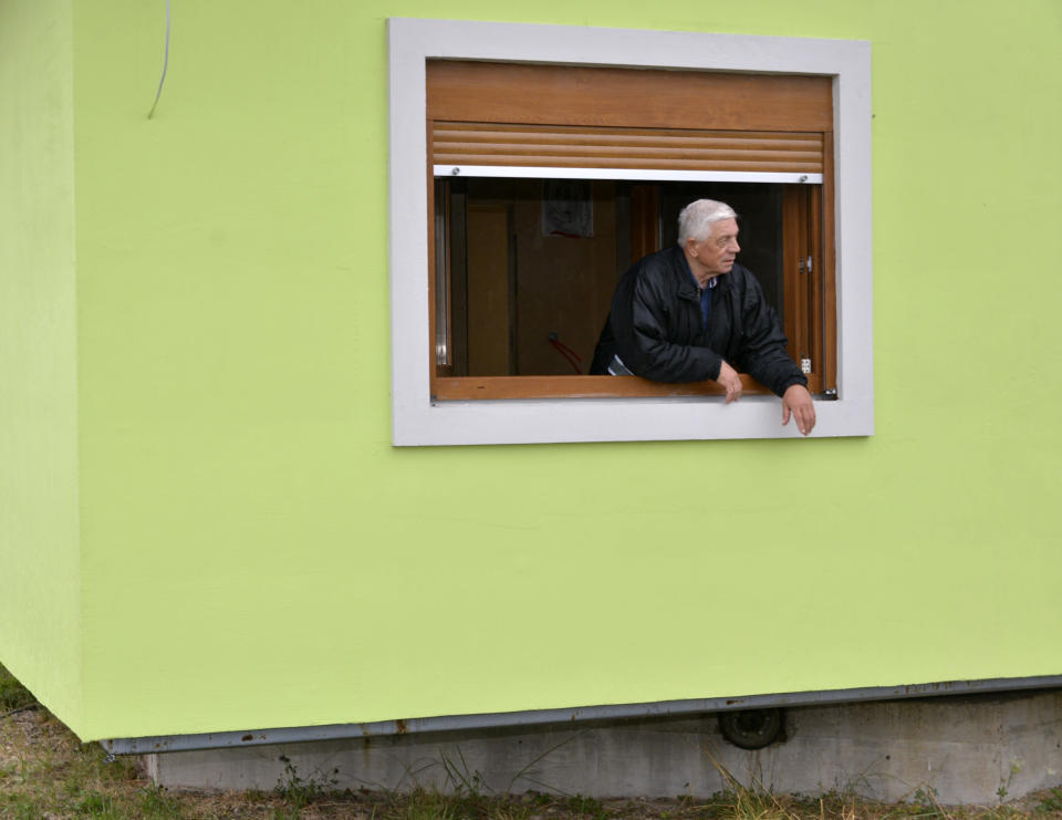 Vojin Kusic's stands on window of his rotating house in a town of Srbac, northern Bosnia, Sunday, Oct. 10, 2021. The house designed and built by 72-year-old Vojin Kusic, with its green façade and red metal roof, can rotate a full circle to satisfy his wife's shifting desires as to what she should see when she looks out of the windows of her home. (AP Photo/Radivoje Pavicic)
