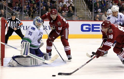 Phoenix Coyotes' Mikkel Boedker (89), of Denmark, tries to get off a shot while being defended by Vancouver Canucks' Kevin Bieksa (3) as Canucks' Cory Schneider (35) and Coyotes' Antoine Vermette (50) look on during the second period in an NHL hockey game, Tuesday, Feb. 28, 2012, in Glendale, Ariz. (AP Photo/Ross D. Franklin)