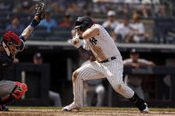 New York Yankees' Luke Voit, right, ducks under a wild pitch while New York Mets catcher Tomas Nido looks down during the fifth inning of the first baseball game of a doubleheader on Sunday, July 4, 2021, in New York. (AP Photo/Adam Hunger)