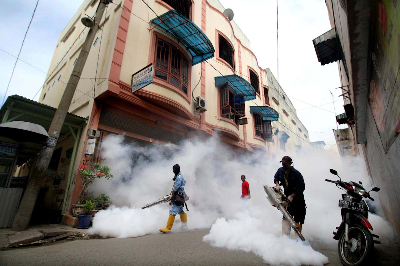 City officers conduct mosquito fogging to combat dengue at a residential complex in Lhokseumawe, Indonesia Aceh province, October 26, 2016 in this picture taken by Antara Foto. Antara Foto/Rahmad/via REUTERS ATTENTION EDITORS - THIS IMAGE WAS PROVIDED BY A THIRD PARTY. FOR EDITORIAL USE ONLY. MANDATORY CREDIT. INDONESIA OUT. NO COMMERCIAL OR EDITORIAL SALES IN INDONESIA.