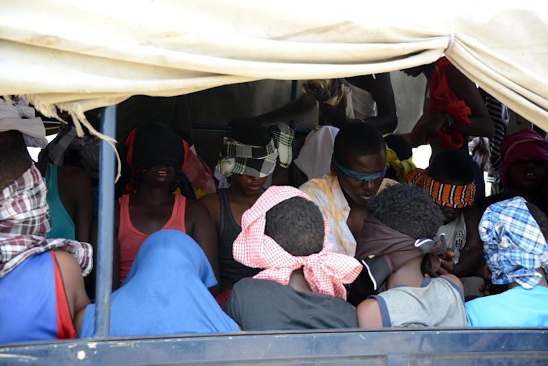 Alleged Al-Shabab fighters are loaded onto a police truck on January 15, 2013 after being arrested during an operation against the fundamentalist group in Mogadishu