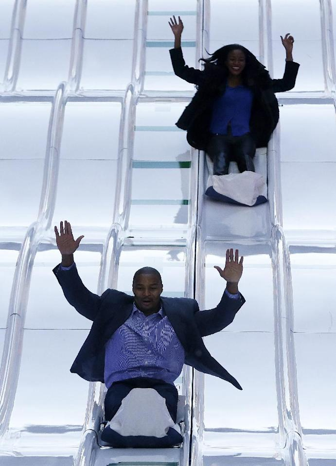 Atlanta Falcons defensive end Osi Umenyiora, bottom, and his fiancee, Miss Universe 2011 Leila Lopes, slide down the toboggan slide during Super Bowl Boulevard festivities Wednesday, Jan. 29, 2014, in New York. The Seattle Seahawks are scheduled to play the Denver Broncos in the NFL Super Bowl XLVIII football game on Sunday, Feb. 2, in East Rutherford, N.J. (AP Photo/Julio Cortez)