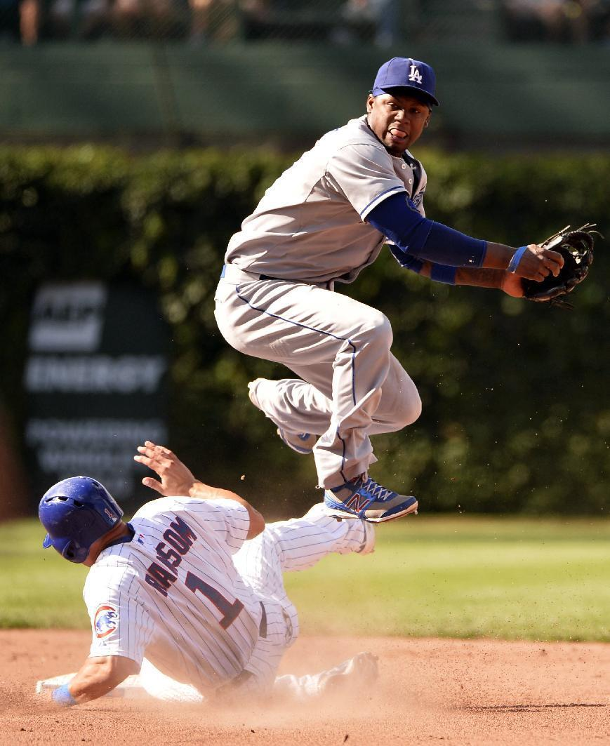 Los Angeles Dodgers shortstop Hanley Ramirez, right, leaps over Chicago Cubs' Cody Ransom (1) after turning a double play on a ground ball hit to second baseman Skip Schumaker by Darwin Barney of a baseball game, Saturday, Aug. 3, 2013, in Chicago. (AP Photo/Brian Kersey)