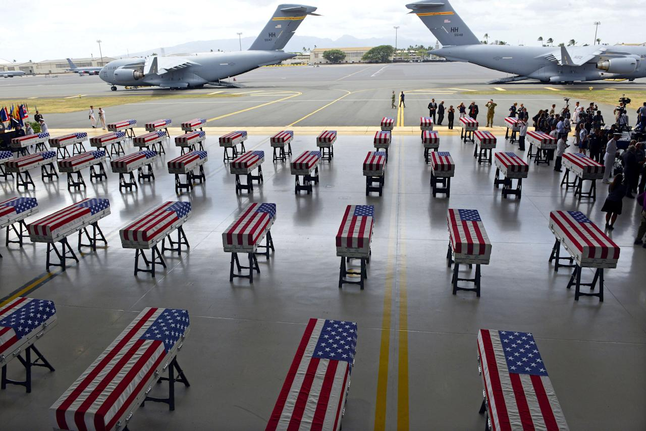 <p>Flag draped transfer cases with the remains of American soldiers repatriated from North Korea are seen during a repatriation ceremony after arriving to Joint Base Pearl Harbor-Hickam, Honolulu, Hawaii, on August 1, 2018. (Photo: Ronen Zilberman/ AFP/Getty Images) </p>