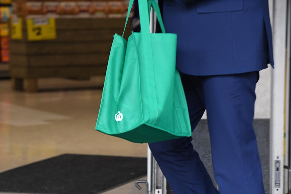 A shopper carrying a reusable shopping bag is seen at a Woolworths supermarket.