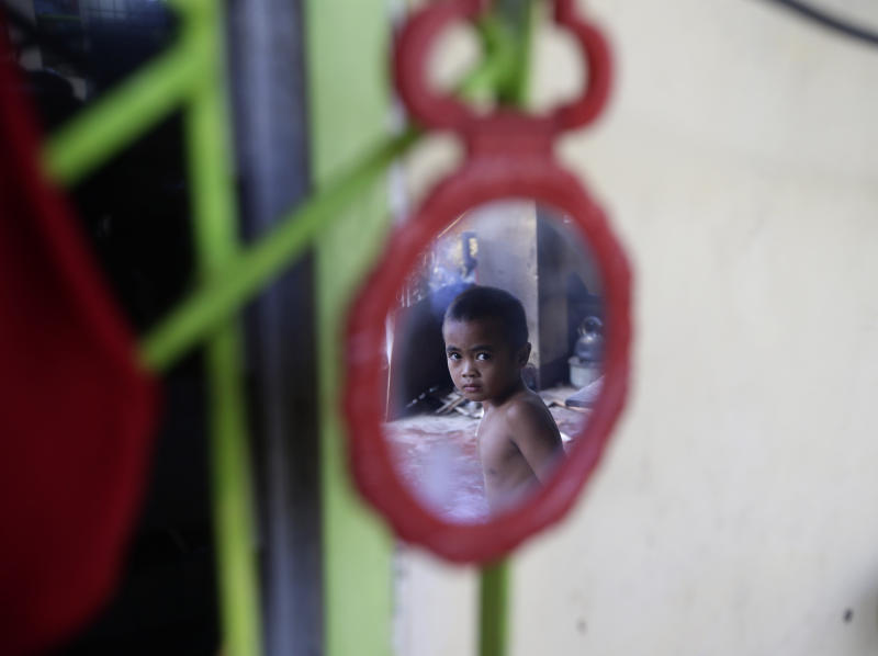 A typhoon survivor is reflected on a mirror as he continues to seek refuge in a typhoon-ravaged public school Friday Nov. 22, 2013 at Tanauan township, Leyte province, central Philippines. Hundreds of thousands of people were displaced by Typhoon Haiyan, which tore across several islands in the eastern Philippines on Nov. 8. (AP Photo/Bullit Marquez)