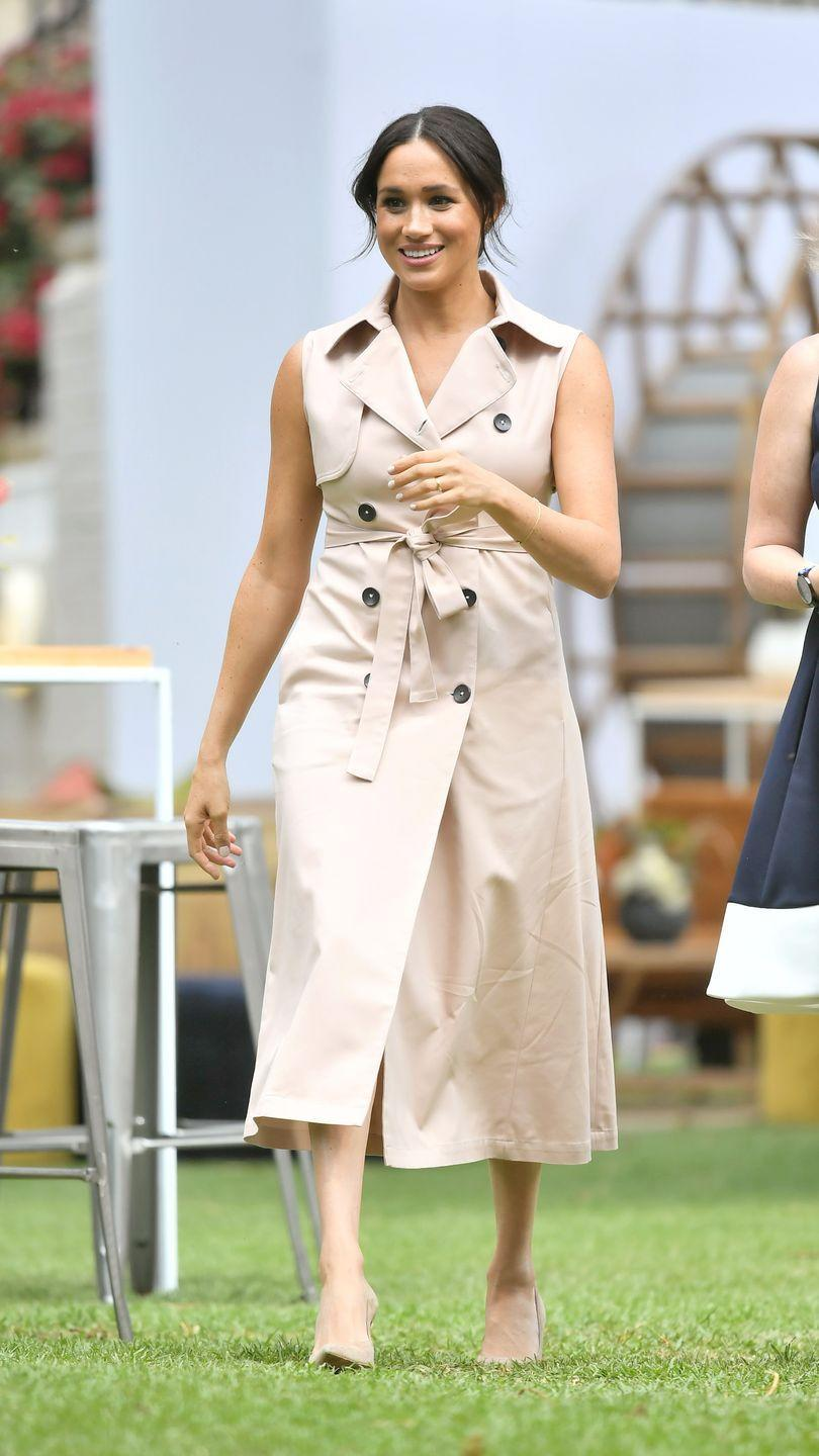 "<p>The Duchess re-wore a pale pink House of Nonie trench dress for a meeting with Graça Machel, the international women's advocate and widow of the late President Nelson Mandela. She was <a href=""https://www.townandcountrymag.com/style/fashion-trends/a22200767/meghan-markle-classic-trench-coat-nelson-mandela-exhibit/"" rel=""nofollow noopener"" target=""_blank"" data-ylk=""slk:last spotted in this dress"" class=""link rapid-noclick-resp"">last spotted in this dress</a> back in July 2018. Meghan also wore nude pumps for the occasion, and styled her hair in a loose bun. </p>"