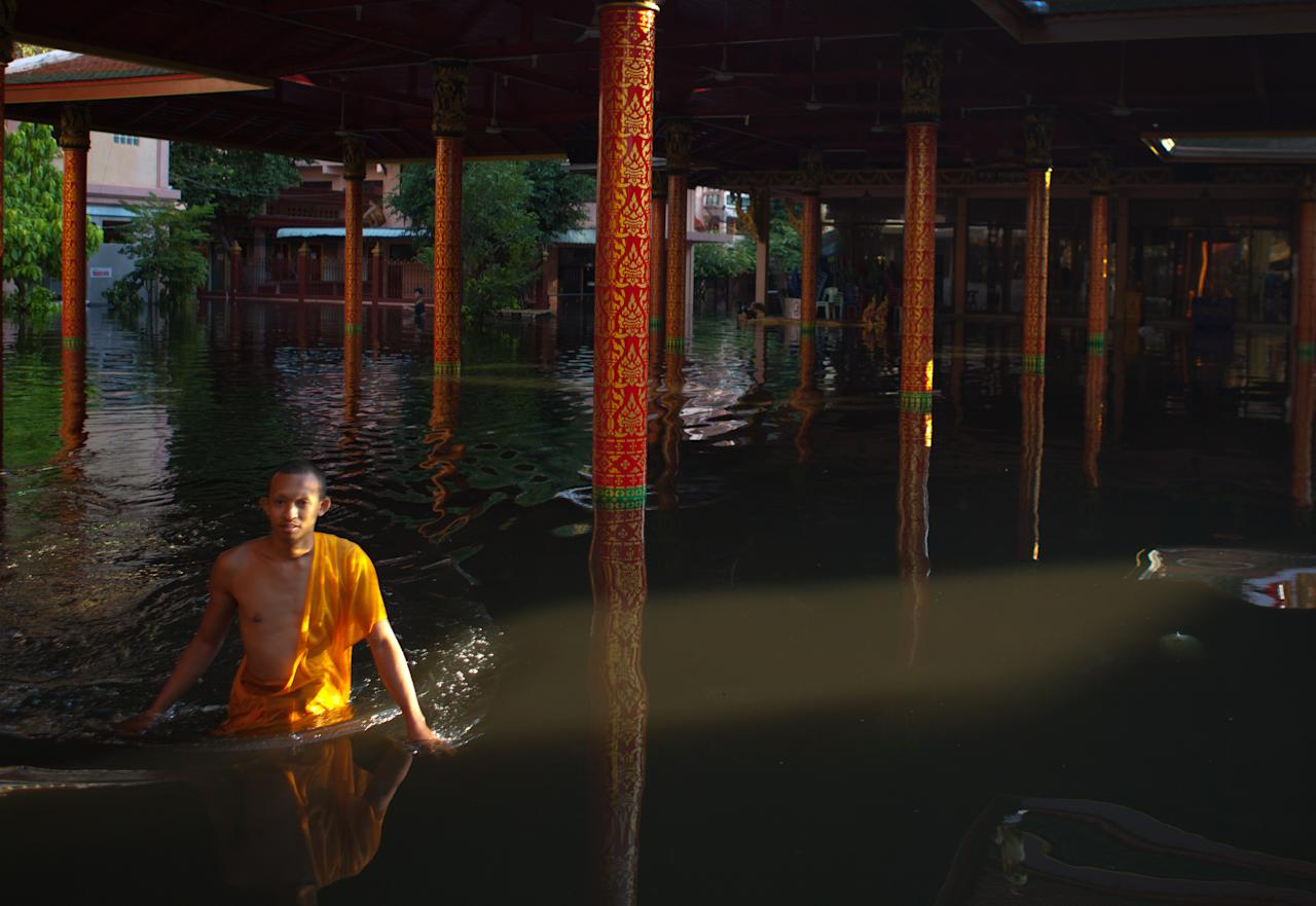BANGKOK,THAILAND - NOVEMBER 1: A Thai monk makes his way on a small boat in the dirty waters at the flooded Laksi temple November 1, 2011 in Bangkok, Thailand. Thousands of flood victims have been forced to take shelter at crowded evacuation centers around the capitol city. Hundreds of factories have been closed in the central Thai province of Ayutthaya and Nonthaburi. Thailand is experiencing the worst flooding in over 50 years which has affected more than nine million people. Over 400 people have died in flood-related incidents since late July according to the Department of Disaster Prevention and Mitigation. (Photo by Paula Bronstein /Getty Images)