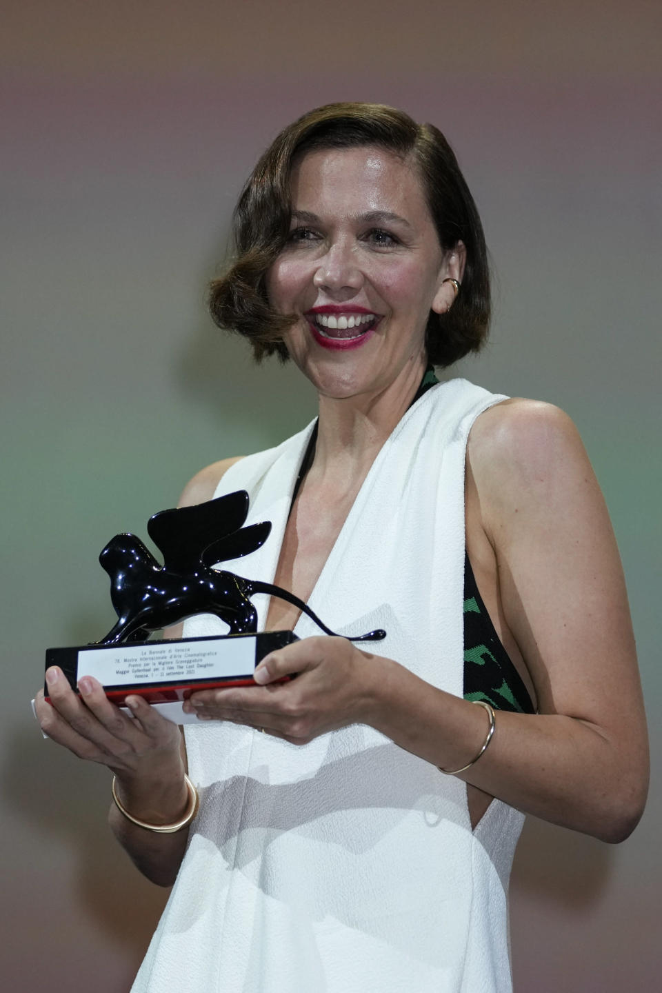 Maggie Gyllenhaal holds the Best Screenplay award for 'The Lost Daughter' onstage at the closing ceremony during the 78th edition of the Venice Film Festival in Venice, Italy, Saturday, Sept. 11, 2021. (AP Photo/Domenico Stinellis)