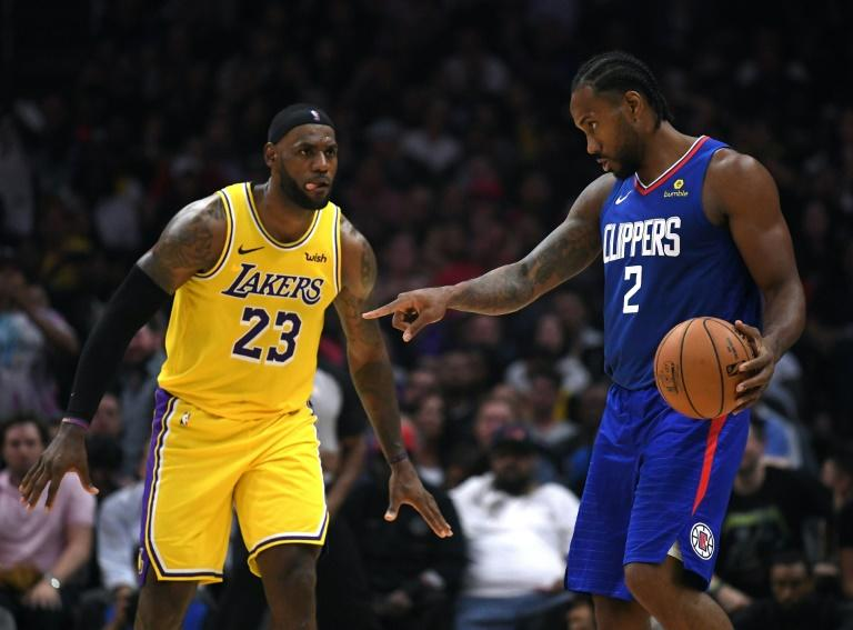 Los Angeles Clippers new addition Kawhi Leonard sets up a play in front of Los Angeles Lakers star LeBron James in the fourth quarter of a 112-102 Clipper win during the NBA season opener for both teams