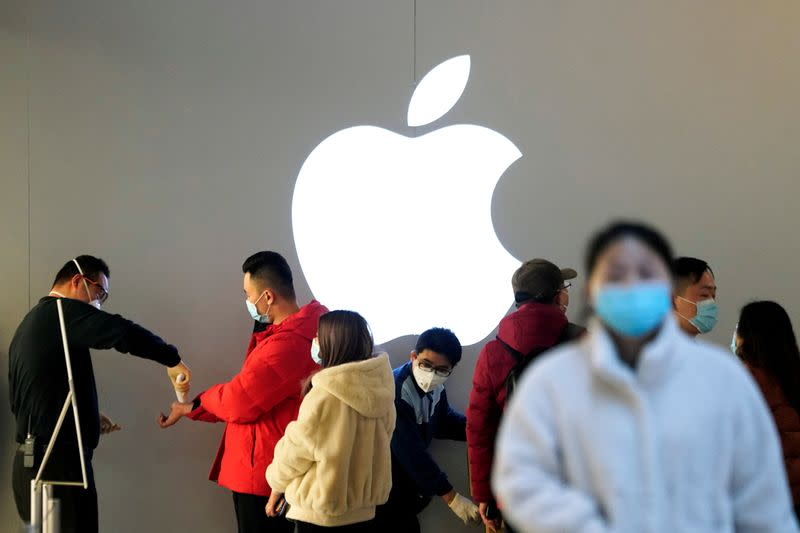 FILE PHOTO: People wearing protective masks wait for checking their temperature in an Apple Store, in Shanghai