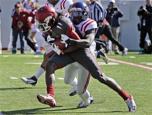 Arkansas wide receiver Cobi Hamilton (11) is brought down by Mississippi defensive back Cobi Hamilton during the first quarter of an NCAA college football game in Little Rock, Ark., Saturday, Oct. 27, 2012. (AP Photo/Danny Johnston)