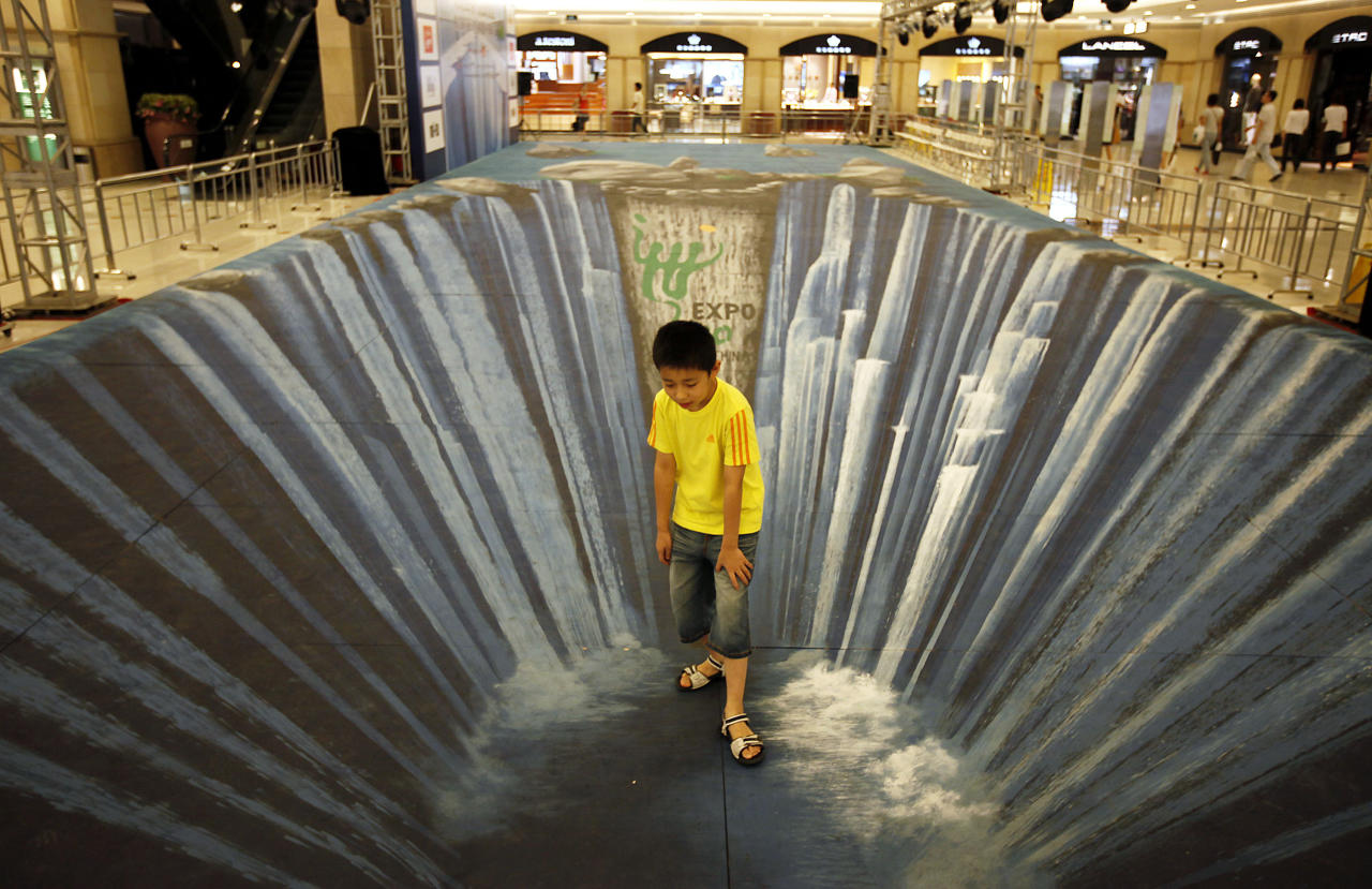 A young visitor stands on a three dimensional visual effect painting at a shopping mall Friday Aug. 14, 2009 in Shanghai, China. The 3D painting with the theme of the Shanghai World Expo is made by Edgar Mueller. (AP Photo/Eugene Hoshiko)