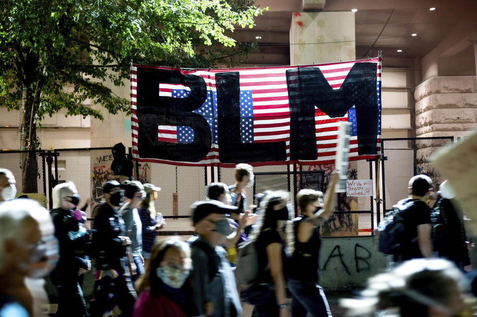 FILE - In this July 31, 2020, file photo, Black Lives Matter protesters march past the Mark O. Hatfield United States Courthouse in Portland, Ore. The federal government deliberately targeted Black Lives Matter protesters via heavy-handed criminal prosecutions in an attempt to disrupt and discourage the global movement that swept the nation last summer in the wake of the police killing of George Floyd, according to a new report released Wednesday, Aug. 18, 2021, by The Movement for Black Lives. (AP Photo/Noah Berger, File)